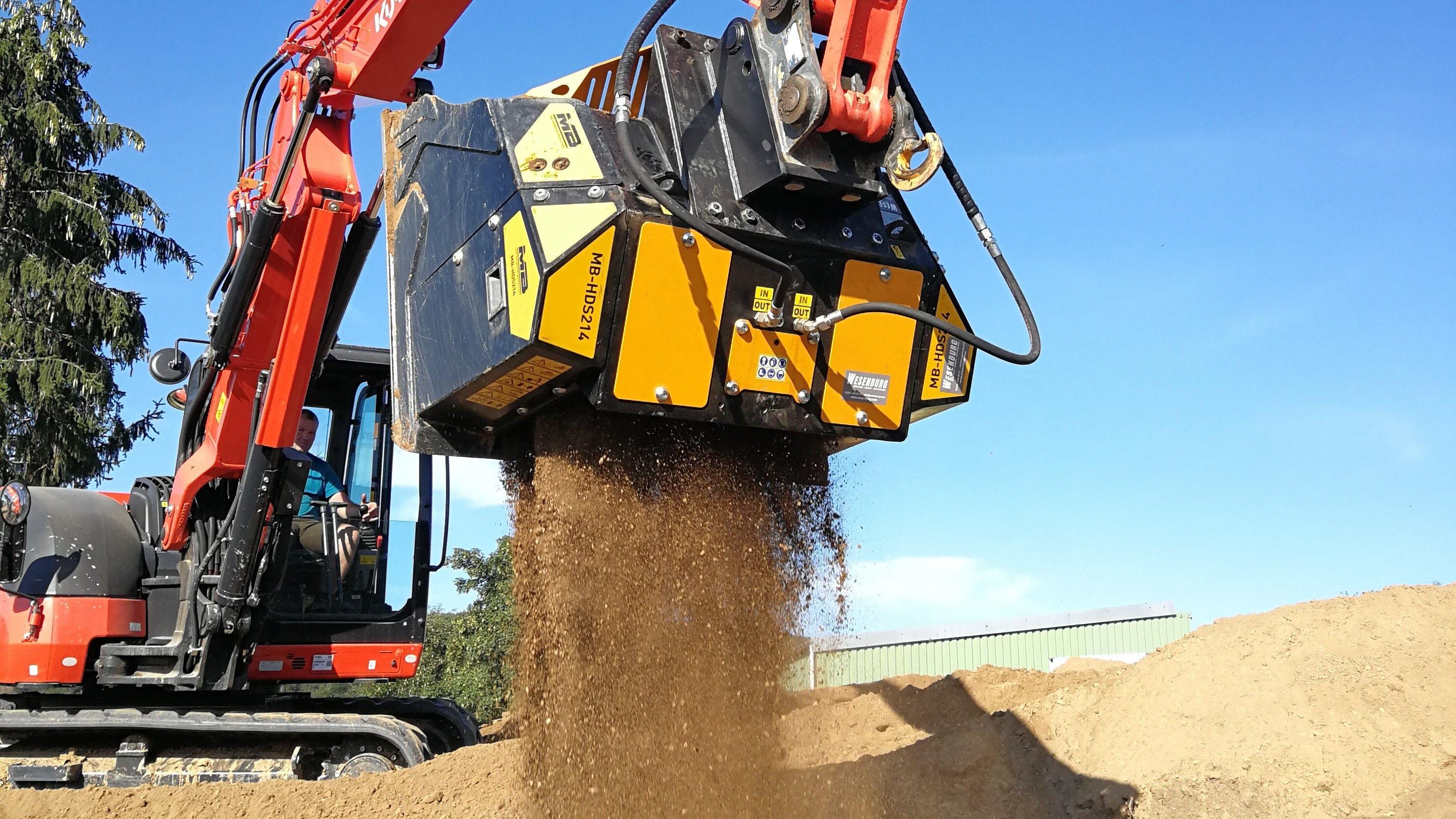 Der Schaufelseparator MB-HDS214 installiert auf einen Kubota KX080-4 siebt Boden mit RE8-Siebwellen mit Hexagonscheiben ab, um dann einen Mutterboden von hoher Qualität zu erhalten, der zur Pflege von Grünflächen eingesetzt wird.