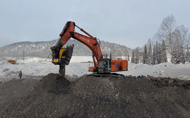 The MB mobile crusher is working on a Hitachi excavator to fix any existing hole in a russian quarry.