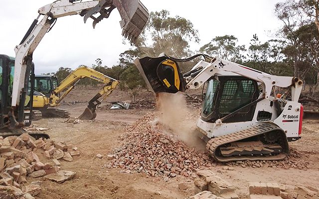 A mini excavator feeding the MB-L140 speeding up the crushing process.