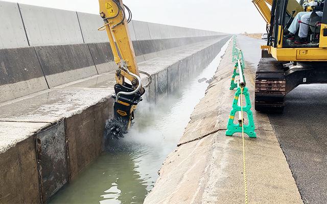 Una fresa Idraulica MB-R800 profila il cemento per l'innalzamento di un argine per proteggere le infrastrutture dalle mareggiate.