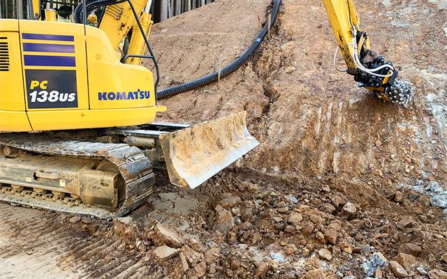 Una fresa idraulica MB-R700 livella le pareti rocciose per l'ampliamento di un tratto di strada in montagna.