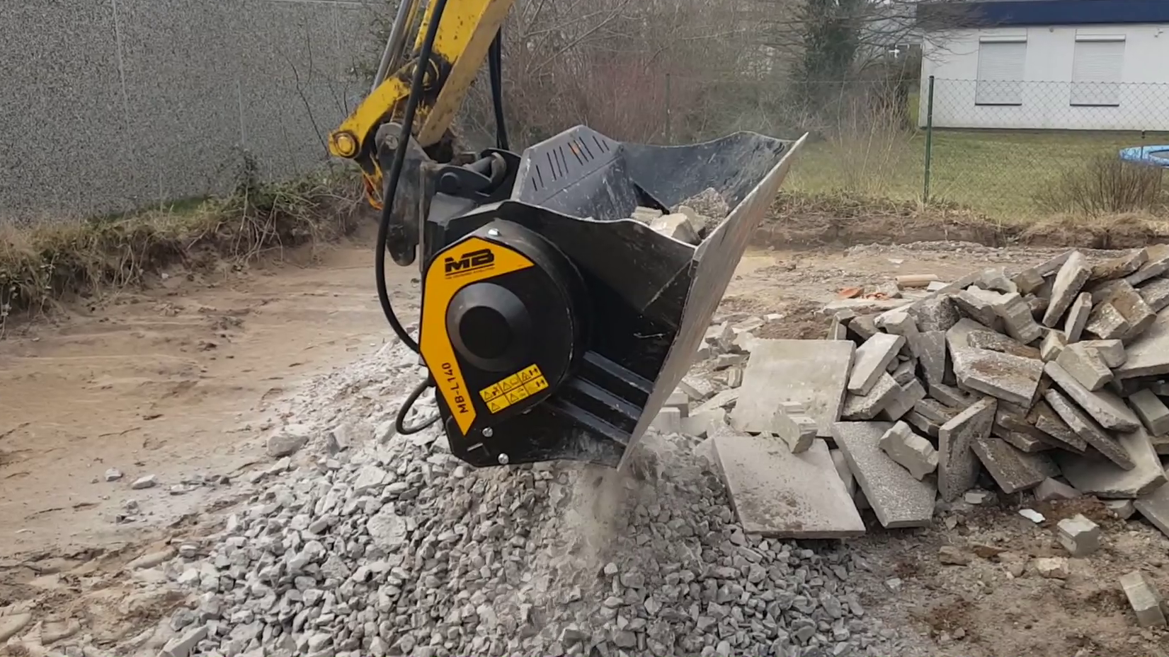 The MB-L140 crusher bucket crushing bricks on a mini-excavator to reuse as fill.